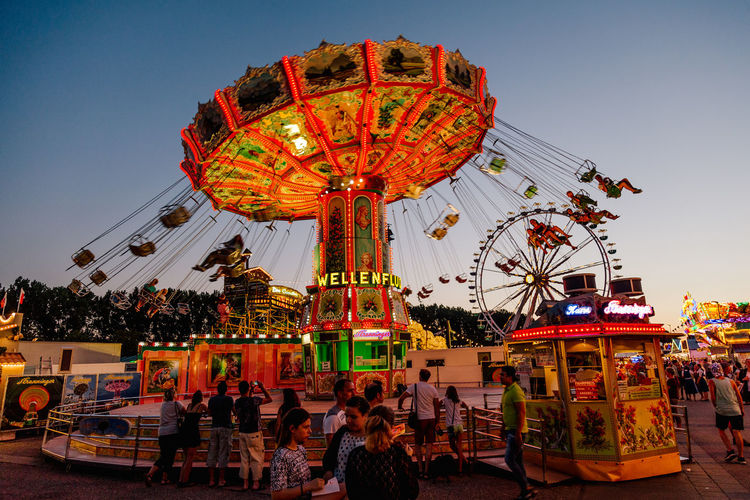 Amusement Park Amusement Park Ride Arts Culture And Entertainment Bavaria Carousel Clear Sky Day Dult Enjoyment Ferris Wheel Group Of People Illuminated Large Group Of People Leisure Activity Lifestyles Merry-go-round Outdoors People Real People Sky