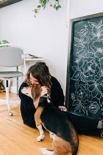 Man with dog sitting on chair at home