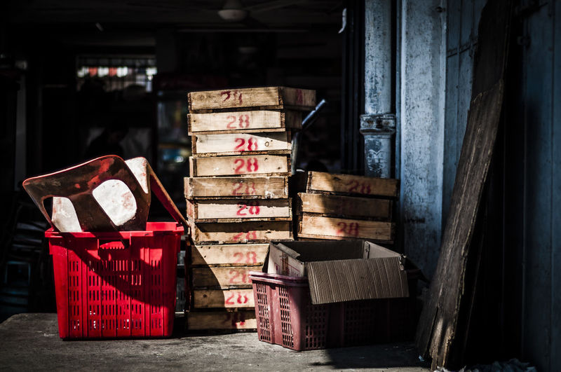 Stack of wooden crates by plastic chair in container in storage room