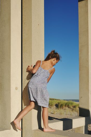 Side view of girl standing on columns against blue sky