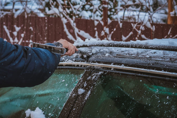 Young teen cleaning snow from the back of the car