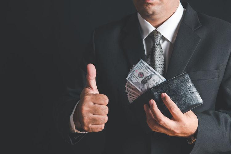 Rich businessman show us dollar banknote in wallet