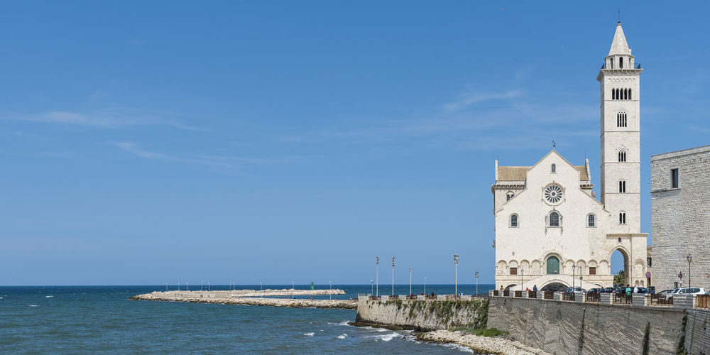 View of building by sea against blue sky