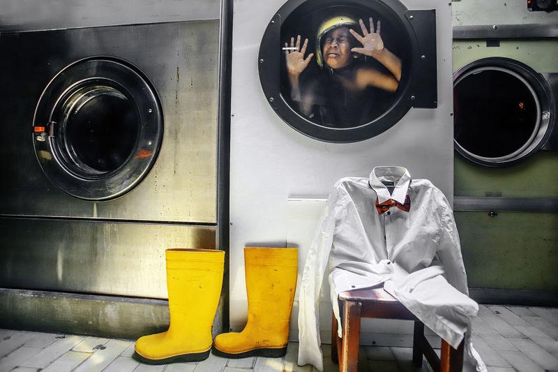 Shirtless boy crying trapped in washing machine