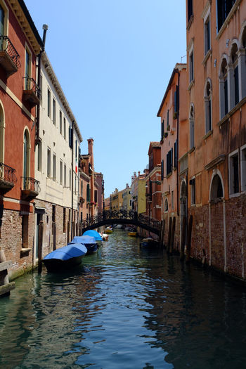 Boats moored in grand canal amidst old buildings against clear sky