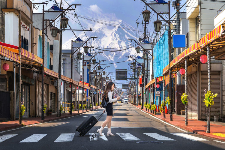 Woman walking on the road in Fujiyoshida with background of Fuji mountain, Japan. Architecture City Building Exterior Built Structure Real People Street Transportation Building One Person Road Lifestyles Full Length Day Adult The Way Forward Women Walking Sign Direction Diminishing Perspective Outdoors