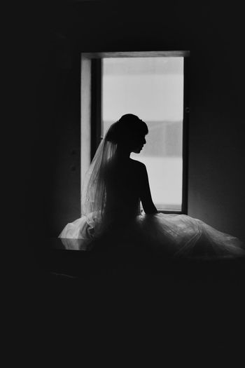 Black and white portrait of a bride One Person Sitting Indoors  Women Adult Real People Lifestyles Side View Bed Window Furniture Domestic Room Looking Young Adult Contemplation Home Interior Hairstyle Dark Waiting Beautiful Woman Bride Wedding Dress Blackandwhite Silhouette