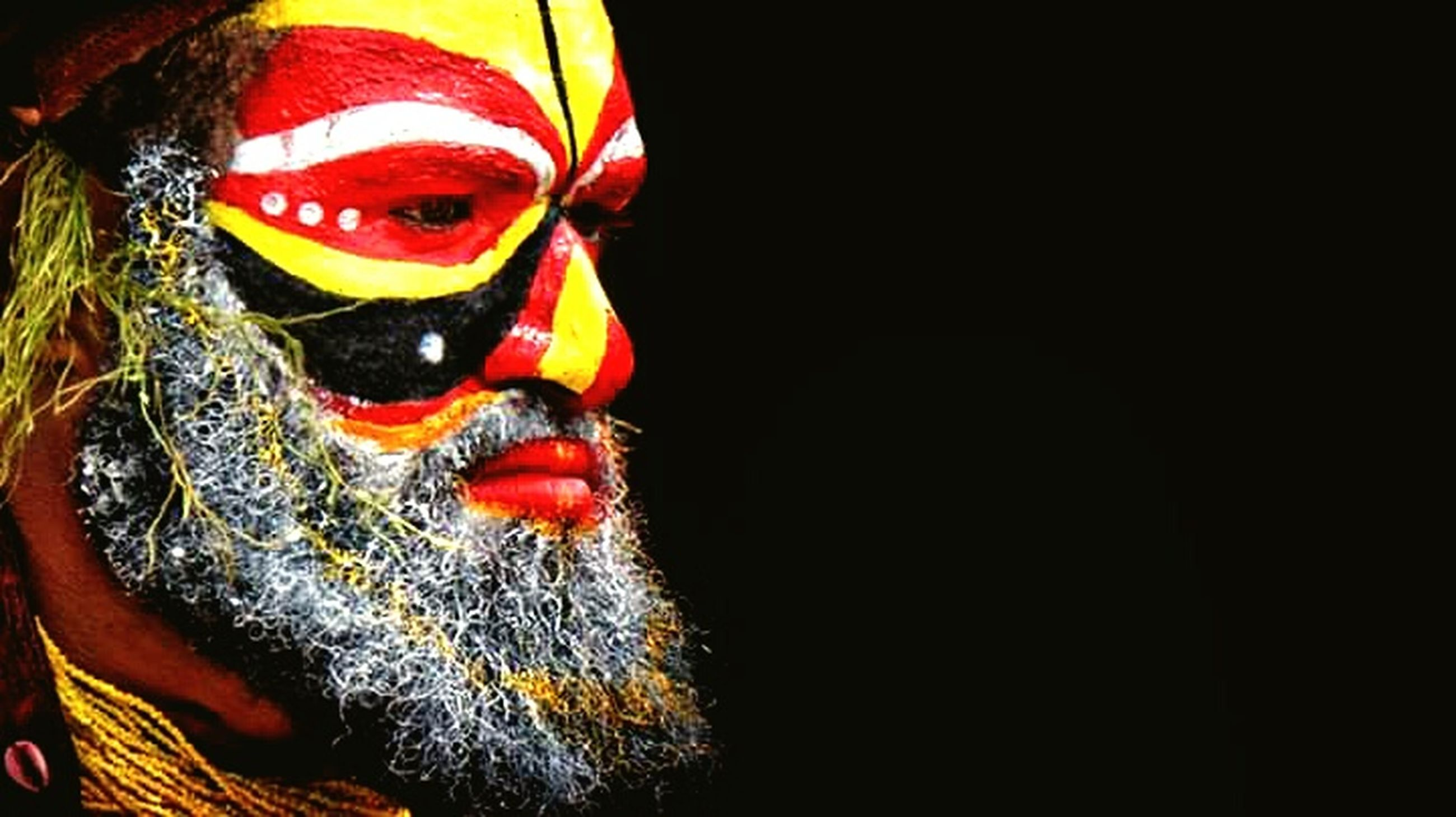 headshot, copy space, celebration, portrait, one person, face paint, multi colored, paint, indoors, black background, close-up, studio shot, traditional clothing, creativity, costume, arts culture and entertainment, clothing, human face