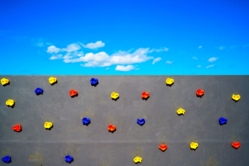 Multi colored climb holds on wall against bright blue sky