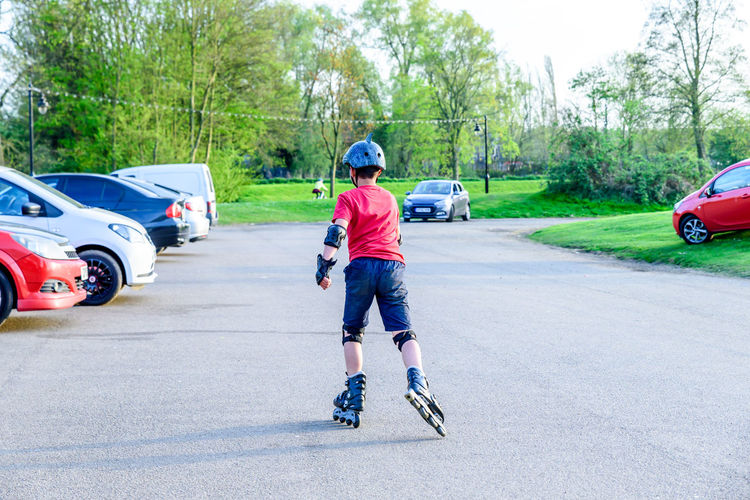 Day view teen boy roller scatting on playground Boy Day Full Length Fun Helmet Outdoors People Playground Real People Rollers Rollerskating Scating Scooter Teen