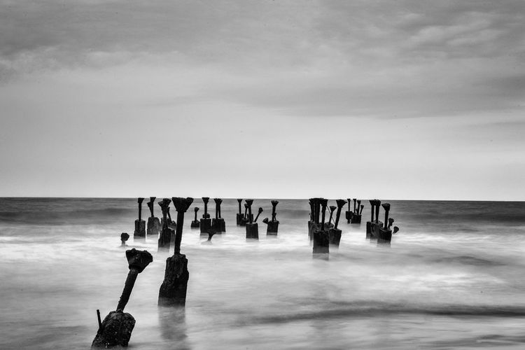 Abandoned poles in sea against sky