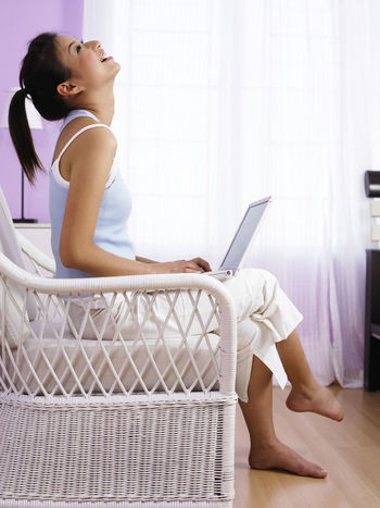chinese woman relaxing at home using laptop 20-25 Years Old Asian  At Home Happiness Sitting Bedroom Casual Clothing Chinese Communication Computer Connection Full Length Indoors  Laptop Lazy Sunday Leisure Activity One Person Rattan Chair Real People Side View Smiling Technology Using Laptop Wireless Technology Young Women