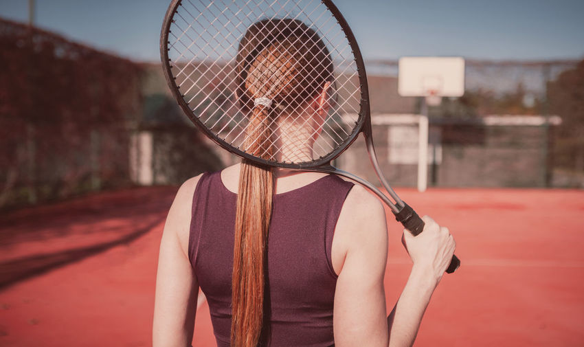 Rear view of woman holding tennis racket