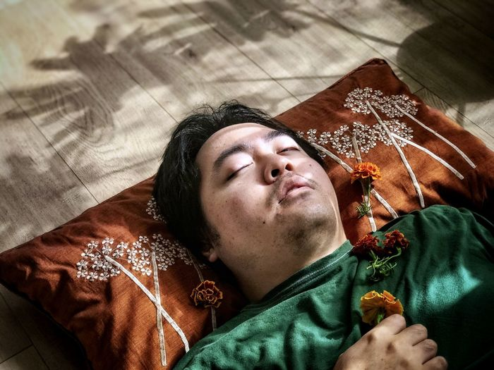 High angle portrait of man lying on brown cushion and holding yellow, marigold flower.