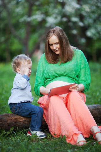 Pregnant Mother Showing Digital Tablet To Son While Sitting On Log At Public Park
