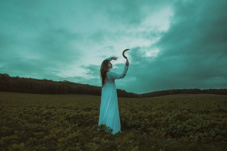 Woman holding umbrella standing on field against sky