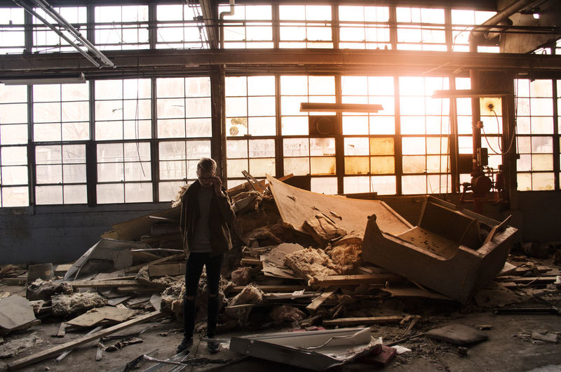 Full length of man standing in abandoned warehouse