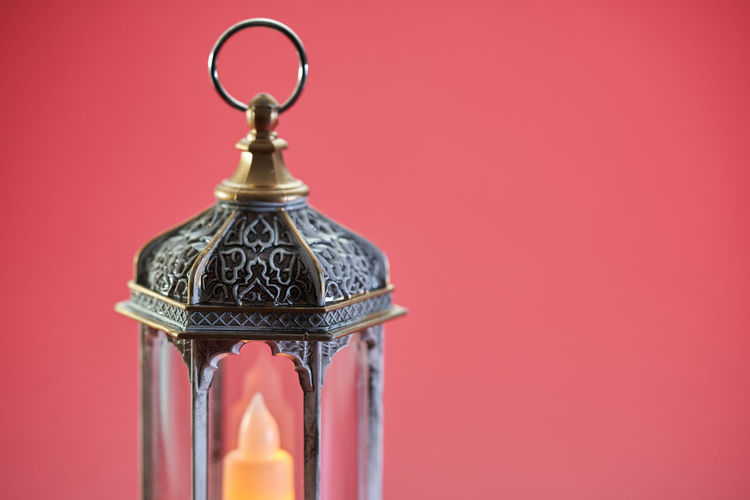 Close-up of electric lamp against red background