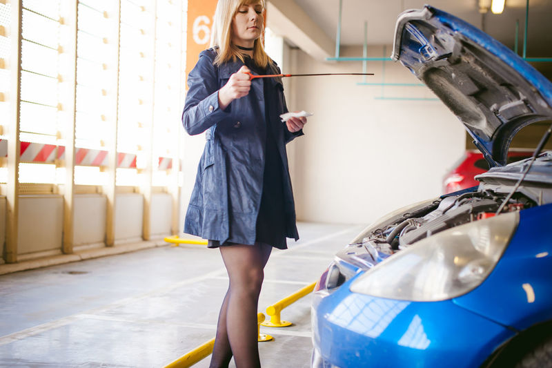 Car Casual Clothing Day Holding Indoors  Lifestyles Mode Of Transport One Person Real People Standing Technology Transportation Wireless Technology Young Adult Young Women