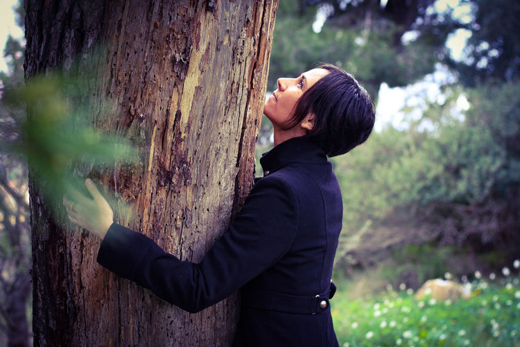 Side view of woman standing by tree trunk