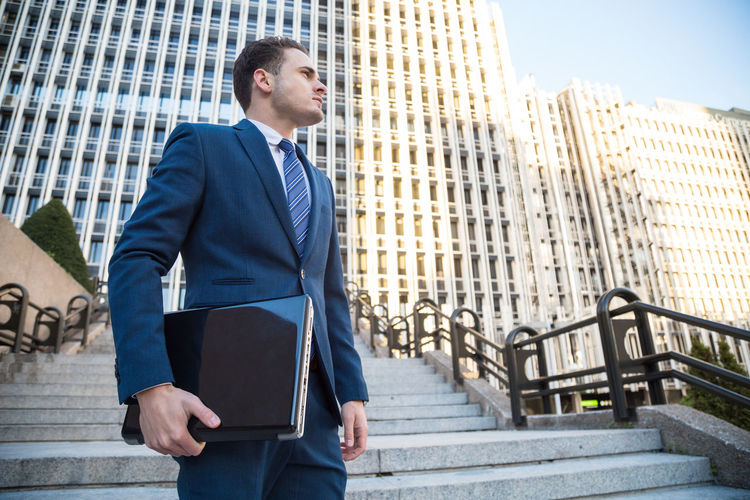 Low angle view of businessman holding folder while standing against skyscrapers