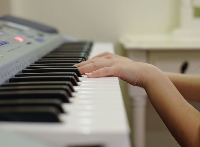 Cropped hands of girl playing piano
