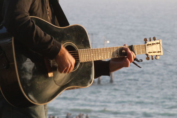 Close-up of man playing guitar at beach