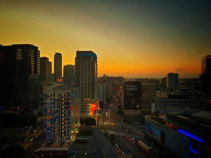 High angle view of city street and buildings against sky during sunset