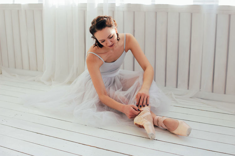 Young woman real ballerina ballet dancer sitting on the floor and tying Pointe shoes One Person Full Length Young Adult Women Real People Indoors  Young Women Sitting Bed Adult White Color Beautiful Woman Lifestyles Beauty Front View Looking Down Fashion Clothing Hairstyle Dancer Ballet Ballerina