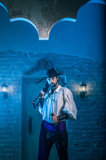 Portrait of man in costume standing against door of abandoned building at night