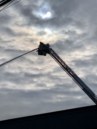 Low angle view of silhouette crane against sky