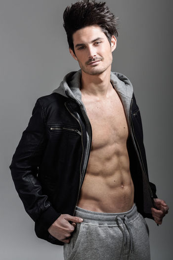 Portrait of athletic man wearing hoodie jacket. Studio shot Abdominal Muscle Beautiful People Body Part Clothing Confidence  Fashion Fashion Model Front View Fully Unbuttoned Gray Gray Background Handsome Lifestyles Looking At Camera Masculinity Men Muscular Build One Person Portrait Standing Strength Studio Shot Young Adult Young Men