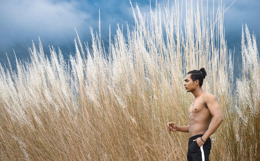 Side view of shirtless young man standing on field against cloudy sky