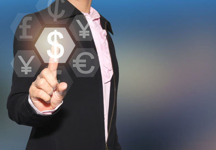 Digital Composite Image Of Businessman Touching Currency Symbols On Device Screen