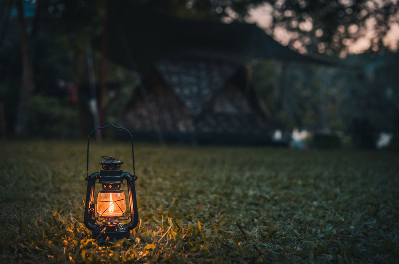 Illuminated oil lamp on field at night