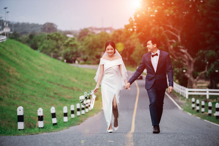 Married couple walking on road in park