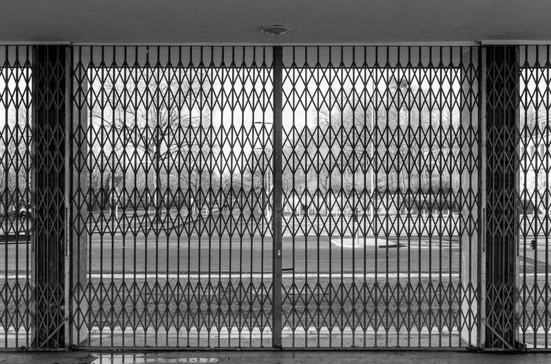 Close-up of metal fence against wall in building