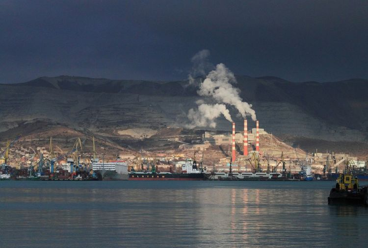 Commercial dock with ships and chimneys emitting smoke by mountain against sky