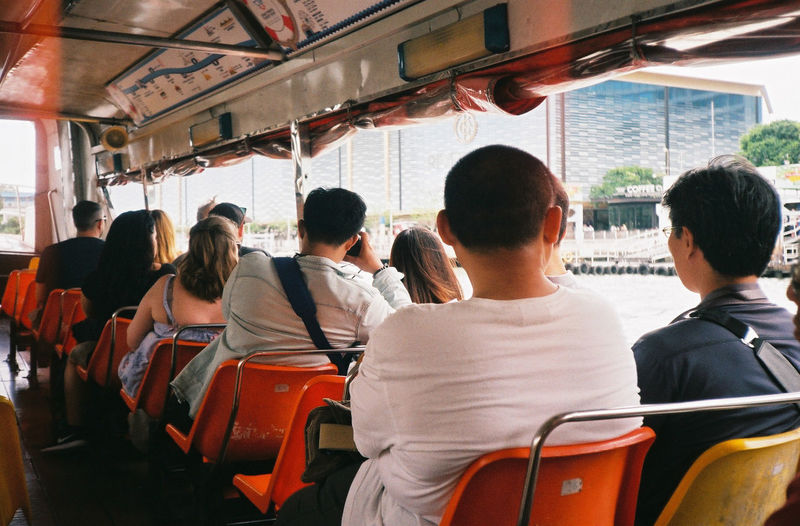 Rear view of people sitting in nautical vessel