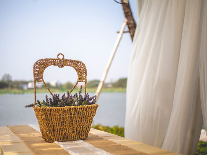 Close-up of wicker basket on table against sea