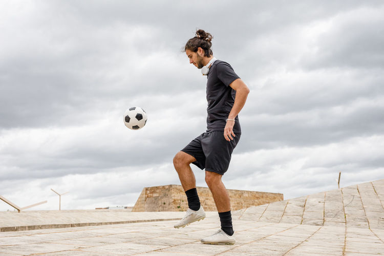Full length of young man playing soccer