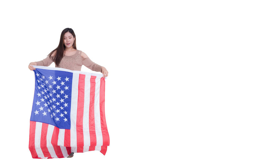 Woman holding flag against white background
