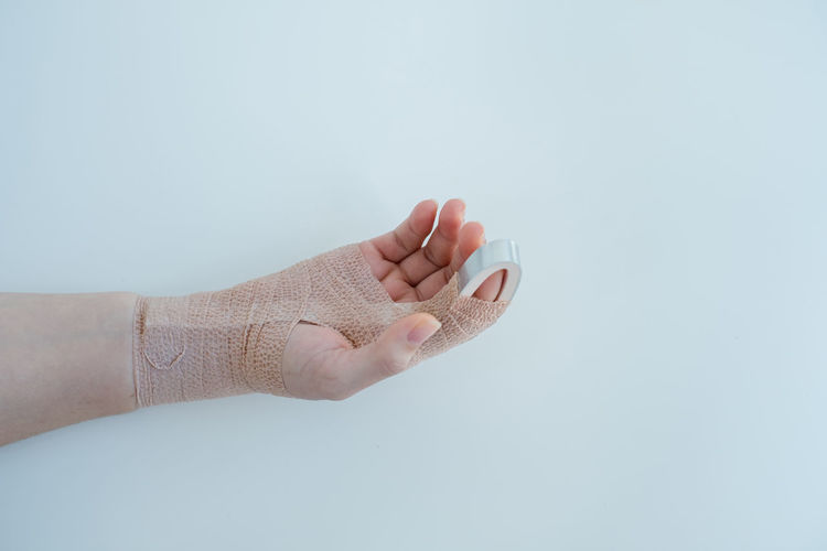 Midsection of person holding hands against white background