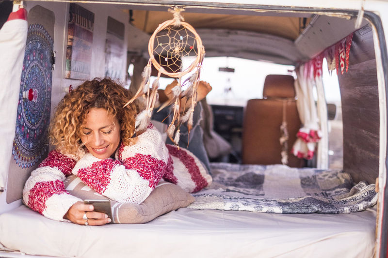 young woman in relaxing moments with old vintage car Bed Mobile Phone Old Vintage Cars Reading Curly Hair Dreamcatcher Lifestyles One Person Outdoor Relaxing Moments Smiling Suggestive Technology Vintage Dress Young Woman