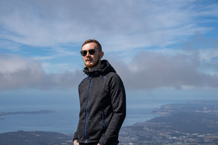 Man wearing sunglasses standing against sky