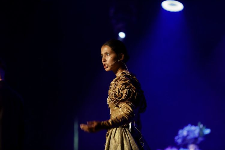 Side view of young woman looking at illuminated stage