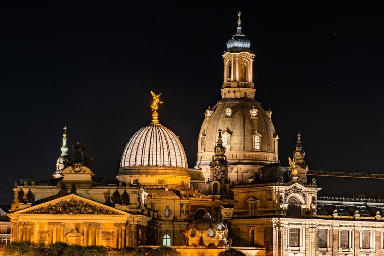 Illuminated historic buildings against clear sky at night