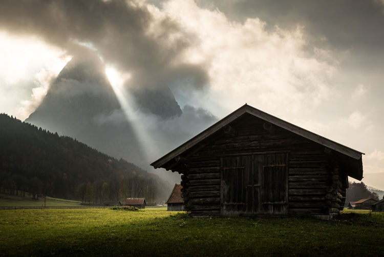 House on field against sky at garmisch-partenkirchen in the german alps