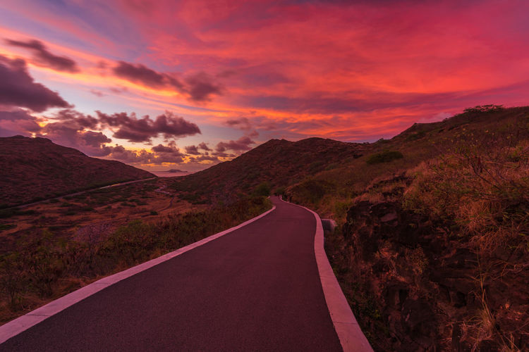 Road amidst landscape against sky during sunset