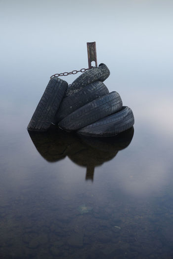 Close-up of rock on lake against sky